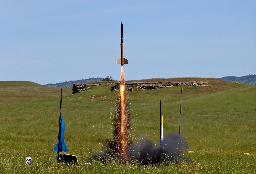 three model rockets lined up in a field and the middle one is taking off with fire and sparks coming out of it