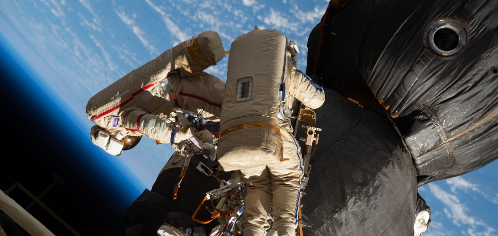 Two astronauts on a space walk fixing a black spacecraft with the Earth behind them.