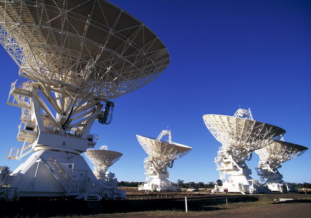 Five radio telescope dishes huddled within the image, all pointing upwards towards the blue sky.