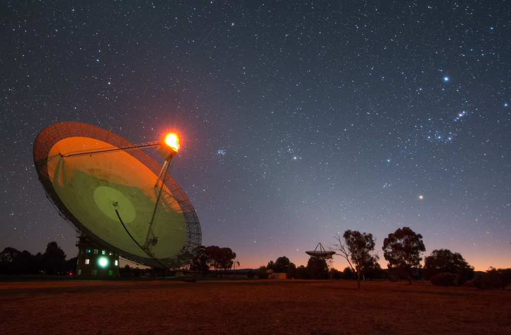 Dusk image of the Parkes radio telescope tilted with the receiver cabin illuminated. In the distance another radio telescope points upwards. The Stars in the sky are also out.