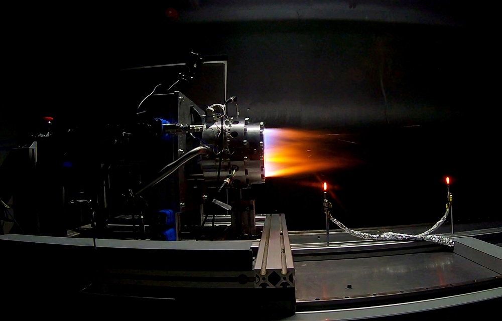 Rocket engine mounted on a rig and being tested. Supersonic jet flames emerge from the exhaust chamber.