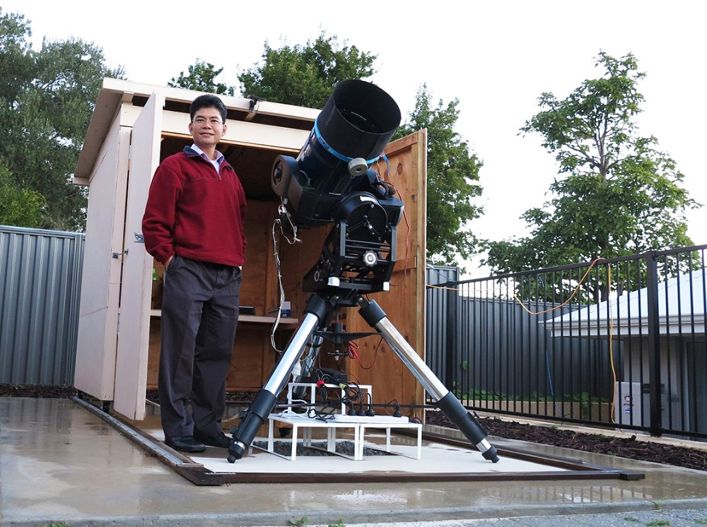Man standing in front of a large telescope with his hands in his pockets. In the background there is a shed where the telescope is storied.