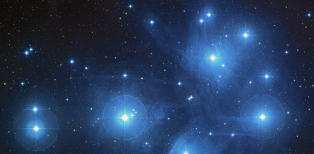 Photo of the Pleiades Seven Sister giant blue stars in the cluster, with surrounding illuminated gases.