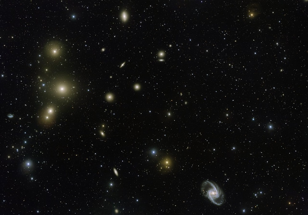 A deep space image showing numerous galaxies, including 10 elliptical galaxies on the left and a main spiral structure on the right.