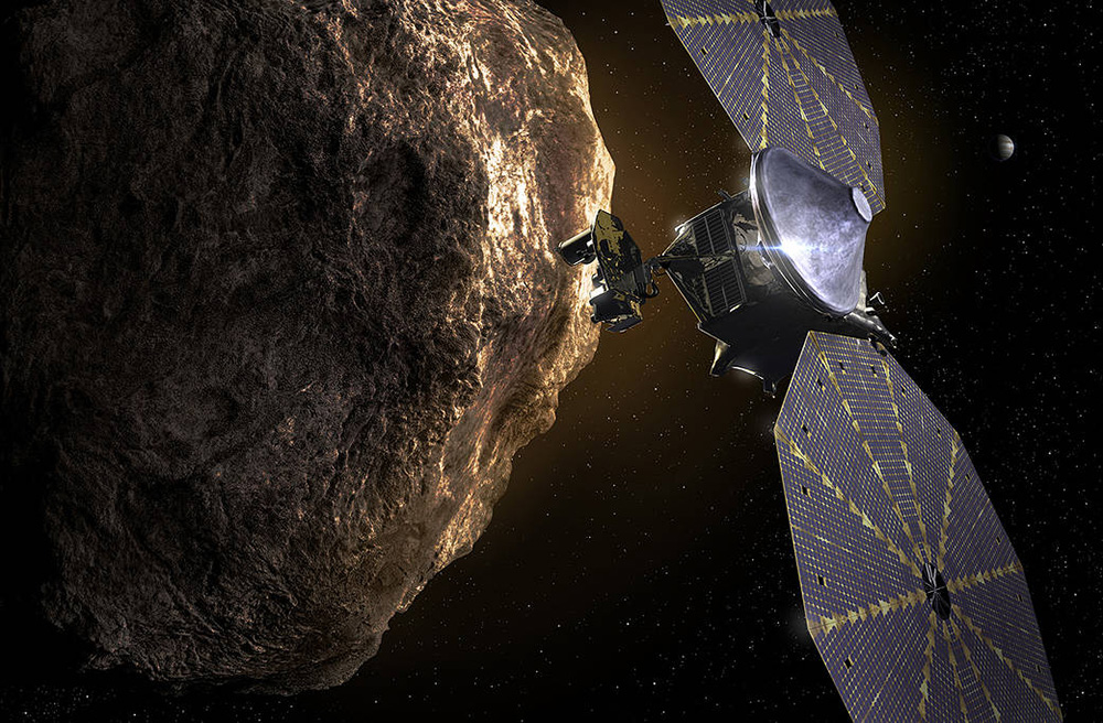 A picture of the Lucy Probe approaching an asteroid. The probe has large decagon shaped solar panels. They are black with gold lines dividing the sections. The probe bus has a large silver funnel shape on top of it and an instrument facing the asteroid. The asteroid is brown and grey and sits in a background with Jupiter in the distance.